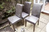 Empty Wooden Chairs In The Garden. Old And Used Leathered Chairs In The Garden. Four Dirty Chairs. H poster
