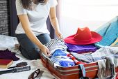 Travel And Vacation Concept, Happiness Woman Packing Stuff And A Lot Of Clothes Into Suitcase On Bed poster