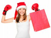 stock photo of boxing day  - Christmas shopping boxing day concept with woman holding shopping bag wearing santa hat and boxing gloves - JPG