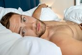 Handsome Man With Abs, Muscular, Hunky Body And Beard Lies Naked In Between White Sheets On Bed.. poster