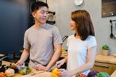 Asian Couple Prepare Food Together. Beautiful Happy Asian Man And Woman Are Cooking In The Kitchen.  poster