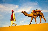 Indian man walking through the desert with his camel poster