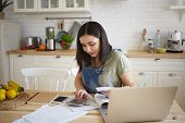 Indoor Shot Of Attractive Young Female Doing Calculations, Managing Home Budget, Sitting At Kitchen  poster