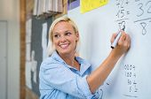 Teacher teaching how to count on whiteboard in classroom. Smiling blonde woman explaining additions  poster
