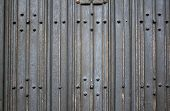 Texture of ancient wooden planks painted in dark grey color with metal rivets poster