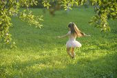 Child With Long Hair In Fashionable Dress, Fashion. Small Girl Play On Green Grass In Summer Park, V poster