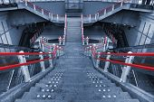 picture of bannister  - Cyanotype symmetrical composition of an entrance in the metro of Rotterdam with red bannisters as the only other color being used in this duotone photograph leading the eyes of the viewer towards the platforms where trains are leaving - JPG