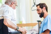 Elderly care nurse helping senior from bed to wheel chair in hospital or nursing home poster