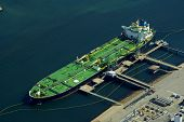 stock photo of fuel tanker  - Aerial of green tanker docked and being refueled - JPG