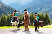 Kids Riding Pony. Child On Horse In Alps Mountains poster