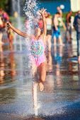 Girl jumping into the fountain at a splash park, shallow focus on water splash poster