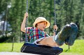 Funny Kid Boy Having Fun With Chain Swing On Outdoor Playground While Being Wet Splashed With Water. poster
