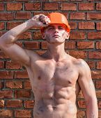 Builder With Muscular Torso And Helmet, Brick Wall On Background. Builder With Strong Muscular Body  poster