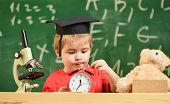 Kid Boy In Academic Cap Near Microscope, Holds Clock In Classroom, Chalkboard On Background. Pupil W poster