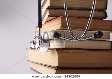 Stethoscope on pile of books isolated. Blue background