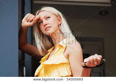 Young woman leaning on the door