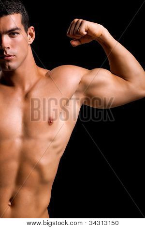 Healthy muscular young man. Isolated on black background.  Shallow DoF with focus on chest and neck.