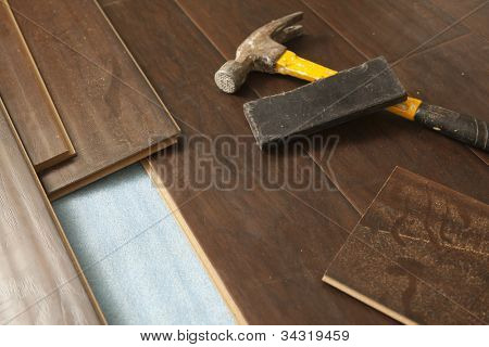 Hammer and Block with New Laminate Flooring Abstract.