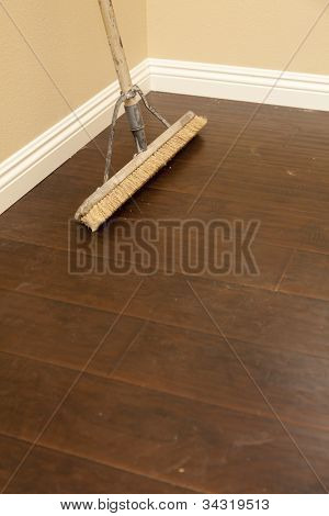 Vassoura de impulso em um piso laminado instalado recentemente e rodapés novos.