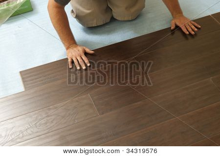 Man Installing New Laminate Wood Flooring Abstract.