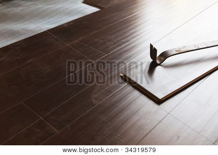 Pry Bar Tool with New Laminate Flooring Abstract.