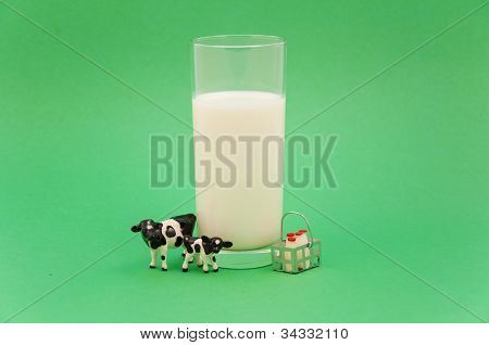 Cow and calf with glass of milk and basket of milk bottles on green background