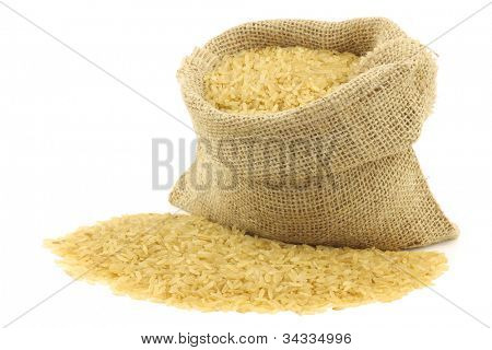 unpolished rice (whole grain) in a burlap bag on a white background