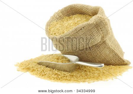 unpolished rice (whole grain) in a burlap bag with an aluminum scoop on a white background
