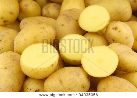 background of dutch seed potatoes  (krieltjes) and a cut one