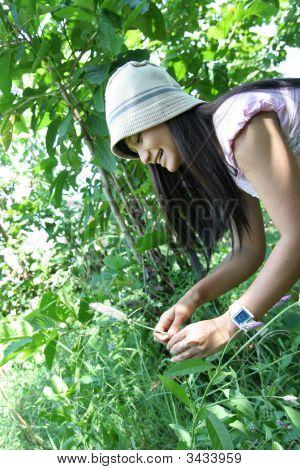 Beautiful Girl Holding Flower At Garden