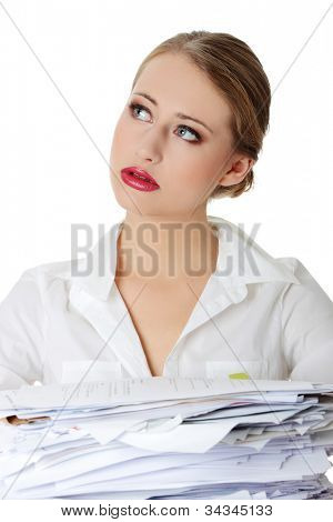 Young upset woman in the office worried, sitting above heap documents and looking up.