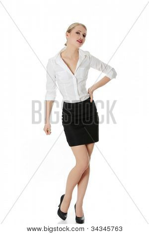 Beautiful young businesswoman standing in frivolous pose with hand on her hip. Elegant office girl in white shirt and black skirt. Isolated on the white background.