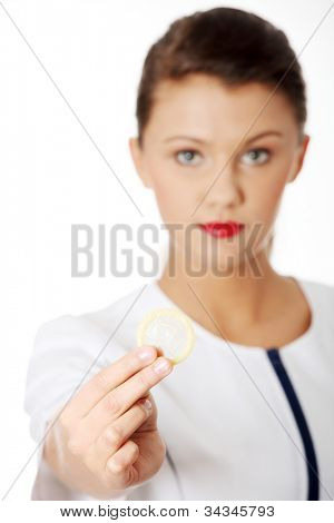 Young woman showing condom which he hold in her hand. Serious brunette who prefer safe pleasure and protection. Isolated on the white background.