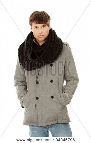 Young, dark-haired, handsome men standing with hands in the pockets, wearing winter coat and warm, black scarf. Isolated on the white background.