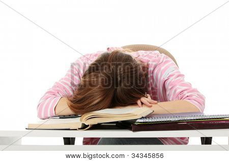 Tired student girl is sleeping on books and files, on the desk. Isolated on the white background.