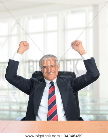 Businessman seated at his office desk with his fists in the air to celebrating a closed deal.