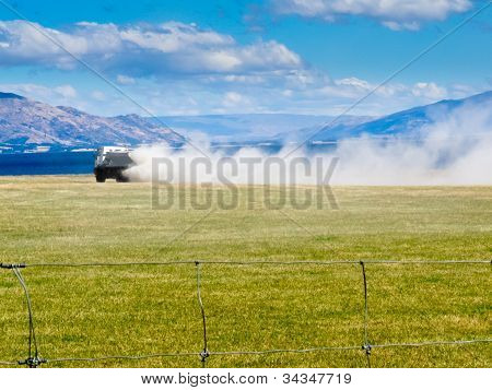 Truck spreading fertilizer on pasture meadow