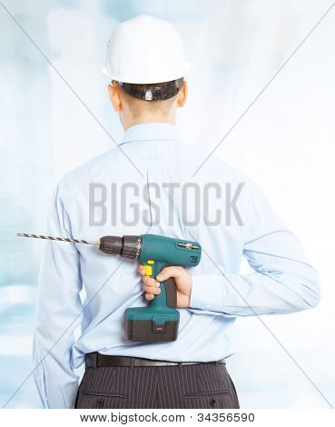 Male worker in a white hard hat holds a cordless drill