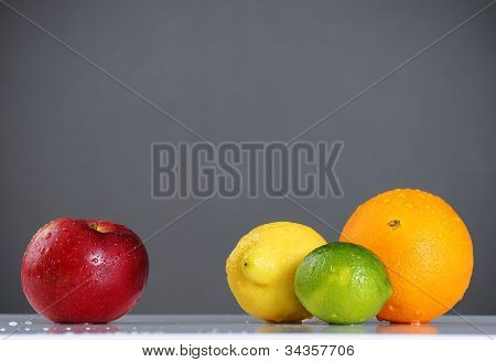 Apple Compared To Citrus Fruits Over Grey