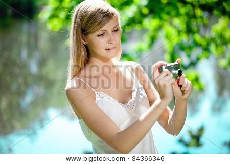 Beautiful smiling woman with a camera in his hands, outdoors