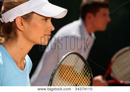 Young woman and man playing mixed doubles tennis game, side view.