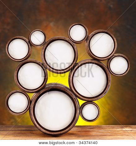 Abstract design of round shapes in the form of beer barrels on a dark yellow background. Inside the barrels textured watercolor paper.