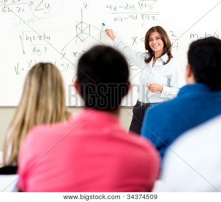 Teacher giving a lecture in a classroom and writing math formulas on the board