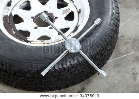 Auto tire and a wrench. Car repair service.