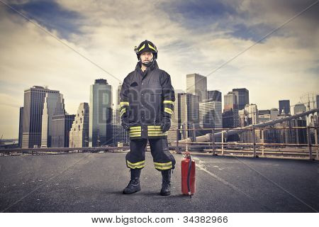 Fireman wearing his uniform with a fire extinguisher beside him and cityscape in the background