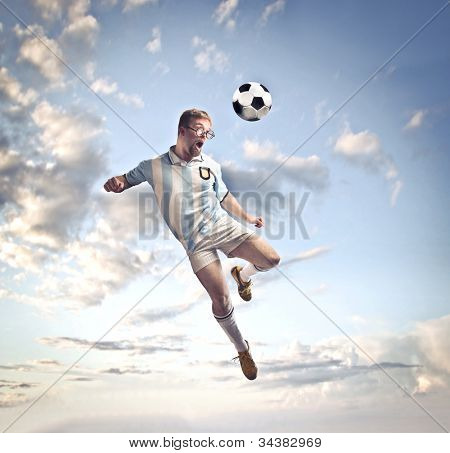 Soccer player head-shooting a football in the sky