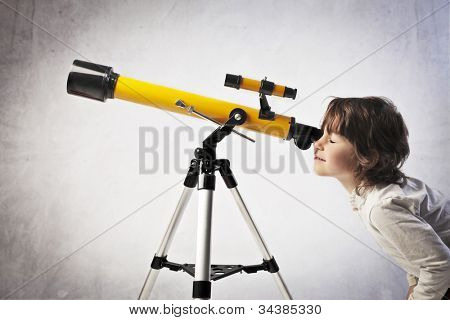 Little girl using a telescope