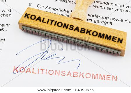 a stamp made of wood lying on a document. german inscription: coalition agreement