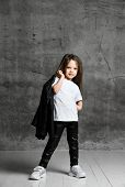 Small Positive Girl In Black And White Rock Style Casual Clothing And White Sneakers Standing And Po poster