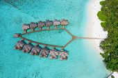 Small island in the Maldives covered by palms and surrounded by turquoise blue waters with with beau poster